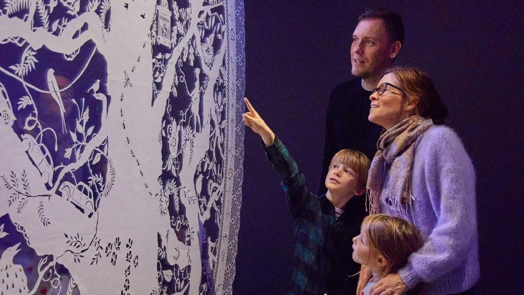 Familie ser på papirkunst