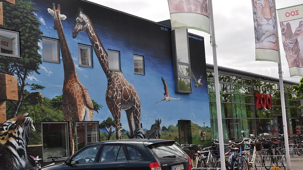 Vægmaleri af giraffer og andre dyr på Odense Zoos facade