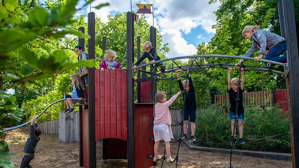 Legeplads med børn som kravler på legetårn